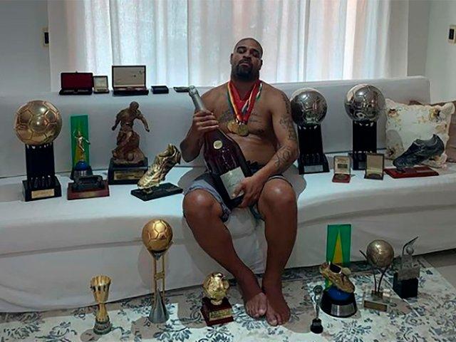 El Emperador posa con sus trofeos, medallas y un champagne. | Foto: Infobae
