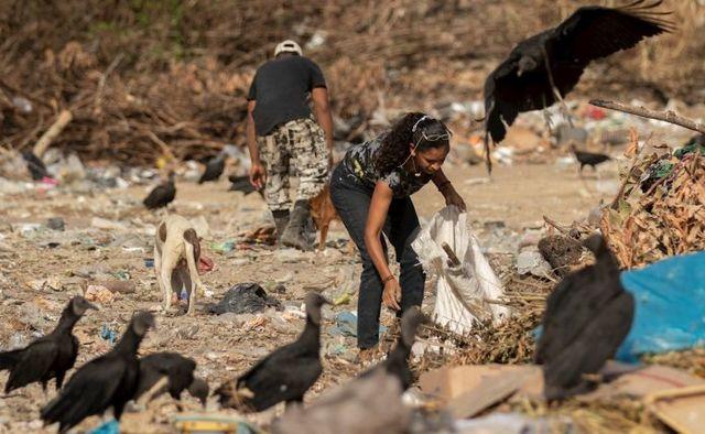 Venezolanos disputan restos de comida con buitres en basurero en Brasil