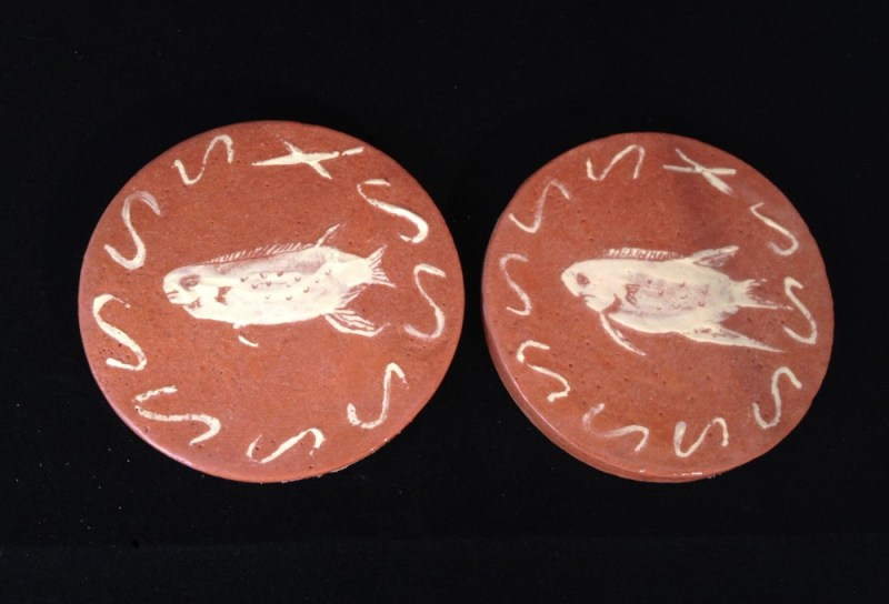 Two cream fish coasters.