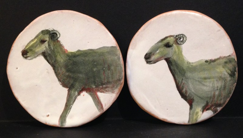 Two earthenware goat decorative items.