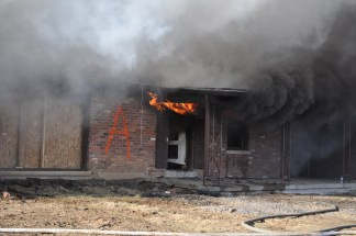 The first flames begin to peek out of the front door of the structure.