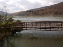 Smoke looms across a lake and bridge.