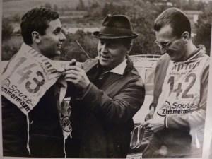 Die Mittelstreckenläufer Karl Eyerkaufer (rechts) und Jürgen May legen Ende der Sechziger Jahre bei einem Sportfest im Rhein-Main-Gebiet mit Hilfe eines Offiziellen die Startnummern an. Eyerkaufer hatte die Flucht des den DDR-Spitzensportler 1967 auf eigene Kosten organisiert. Repro: Nissen