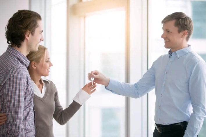 Landlord handing keys to rental proeprty over to new tenants.