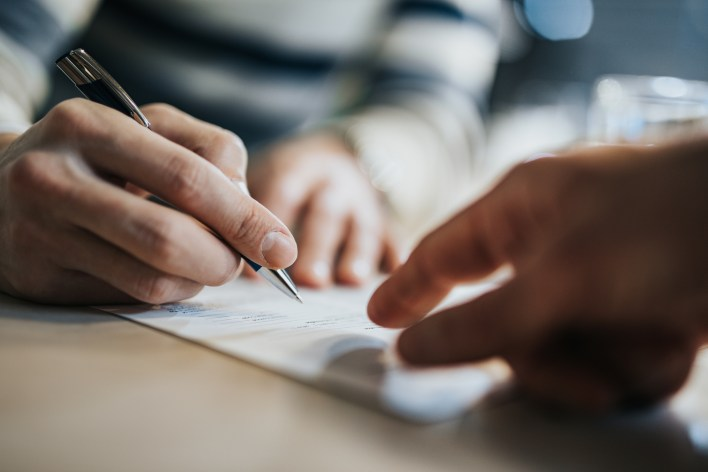 Signatory signing a lease agreement in the office of a landlord as opposed to signing a lease remotely.