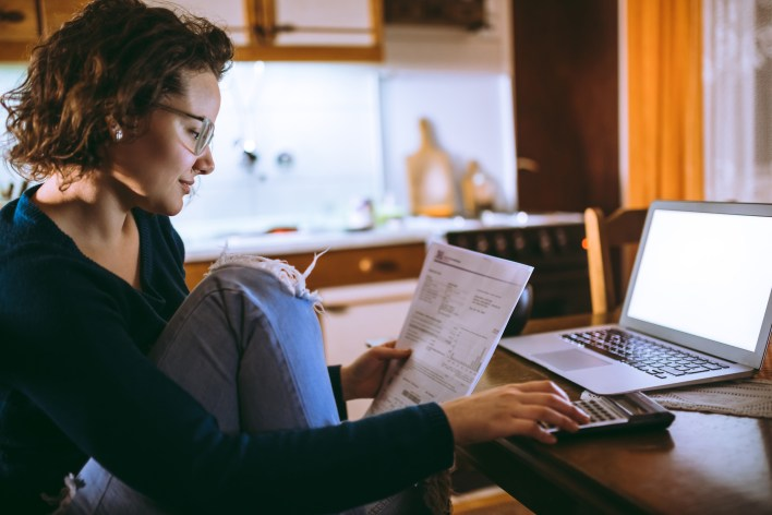 A woman sitting at home and paying bills and rent on her laptop using a software like ClearNow rent collection.