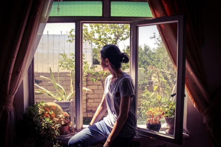 young-woman-sitting-on-ground-floor-windowsill-inside-rented-property-and-looking-outside-at-trees