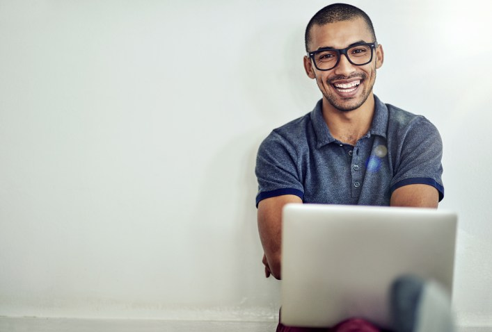 Portrait of a smiling young man using a laptop while sitting on his living room floor at home