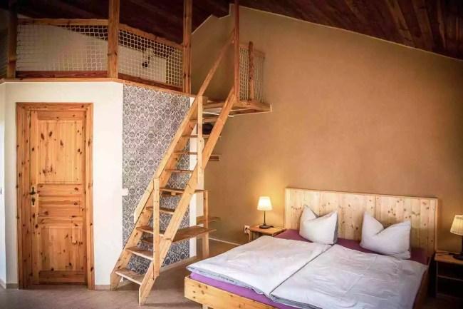 Eines der beiden Zimmer oben mit Stiege zur Empore und Bett dort oben