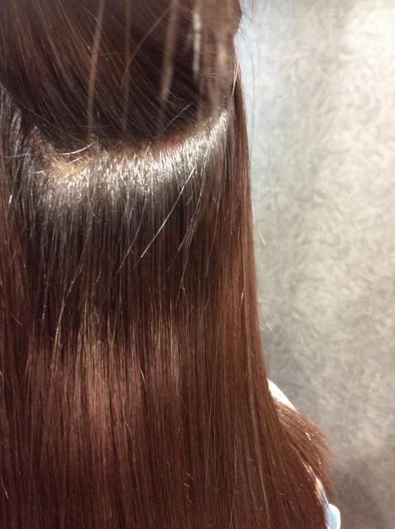 表面の髪の毛を持ち上げて中の状態を写した写真です。縮毛矯正をかけた後の綺麗になった髪です。根元から綺麗に伸びていますね。シットリとした髪の毛が確認出来ます。このくらい回復すれば良いと思います。お客様も満足しているのがよく分かります。