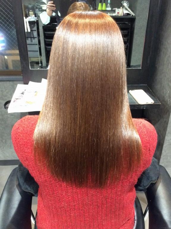 縮毛矯正をした後の仕上がりの画像です。金髪の女性が鏡の前でセット椅子に座っています。髪の毛の状態はトップには天使の輪が出来て肩の部分も光っています。かみのけは全体にツヤツヤサラサラヘアーになっています。しなやかでしっとりした感じが見ただけで分かります。