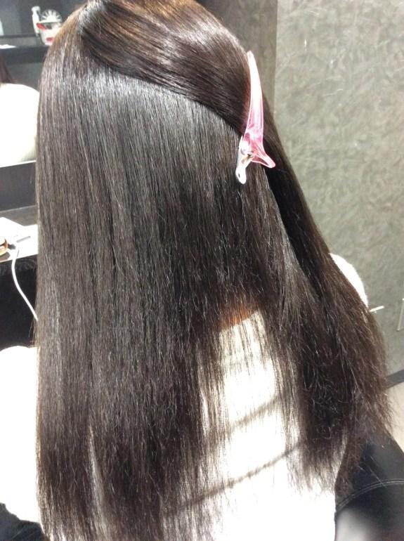 美容室の鏡の前に座っています。後ろから写真を撮りました。髪の毛は頭頂部をダッカールで留めて中の状態が見え易くしています。全て直毛で天使の輪が眩しいです。首筋の髪の毛はありません。穴が空いた状態です。毛先にほんの少しパサパサした髪の毛がみえます。