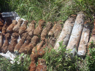 Hundreds of UXO being collected and safely removed from under the foundation for later disposal.