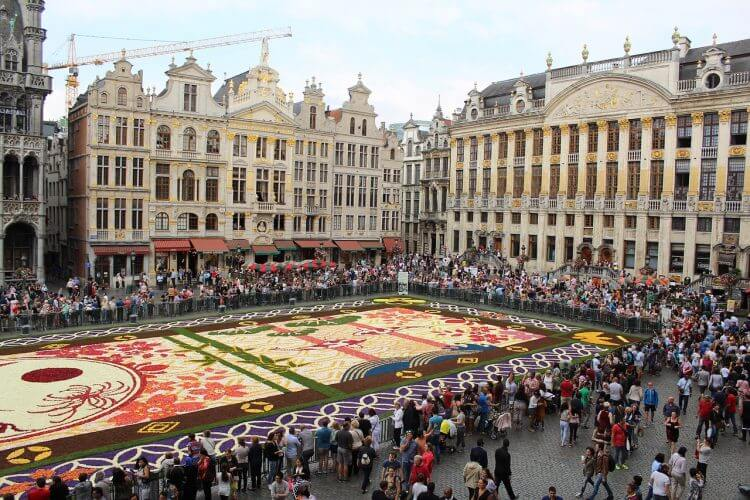 An image of a flower carpet being displayed at La grand place during a festival