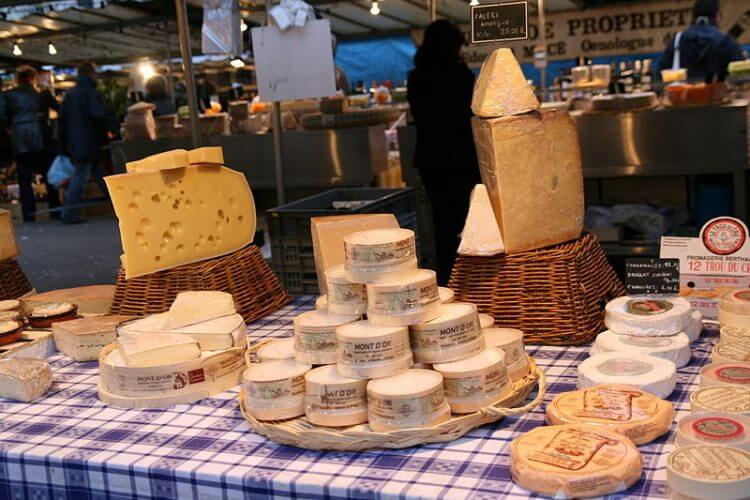 An image of different types of cheese on display at the Marche Bastille in Paris