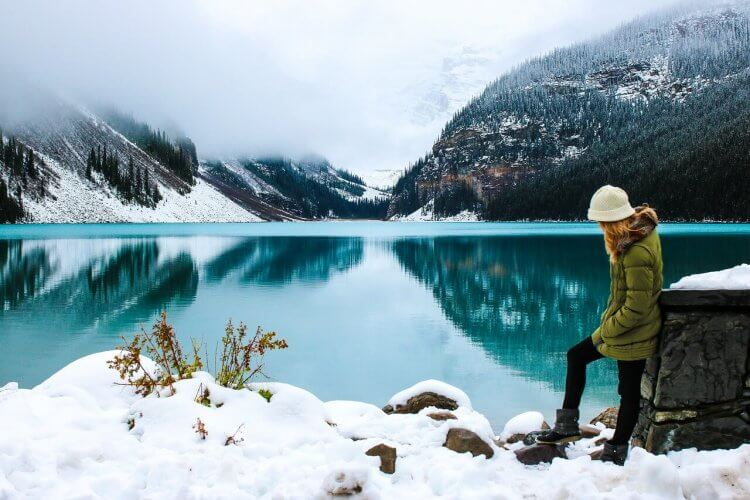 A girl hiking by a lake in winter