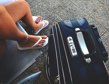 An image of a girl next to a suitcase