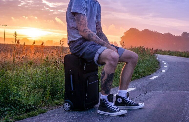An image of a man sitting on a roller-board checked luggage