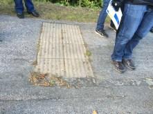 Resten av ett övergångsställe. Ränderna i gatan är borta, men signalen till de blinda är kvar i backen.