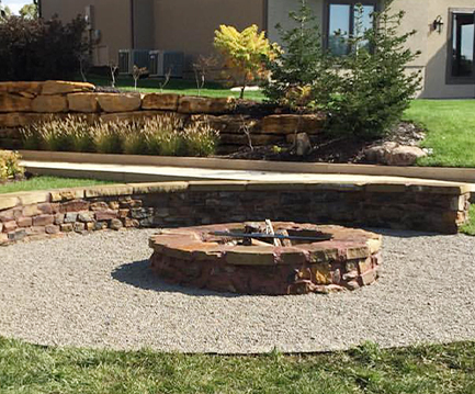 stone fire pit surrounded by small rocks and stone wall