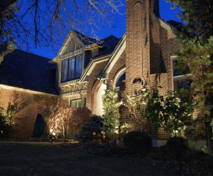 exterior of house with brick siding and tall bushes with lighting