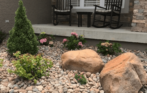 front patio with stone fill pink hydrangeas and small bush