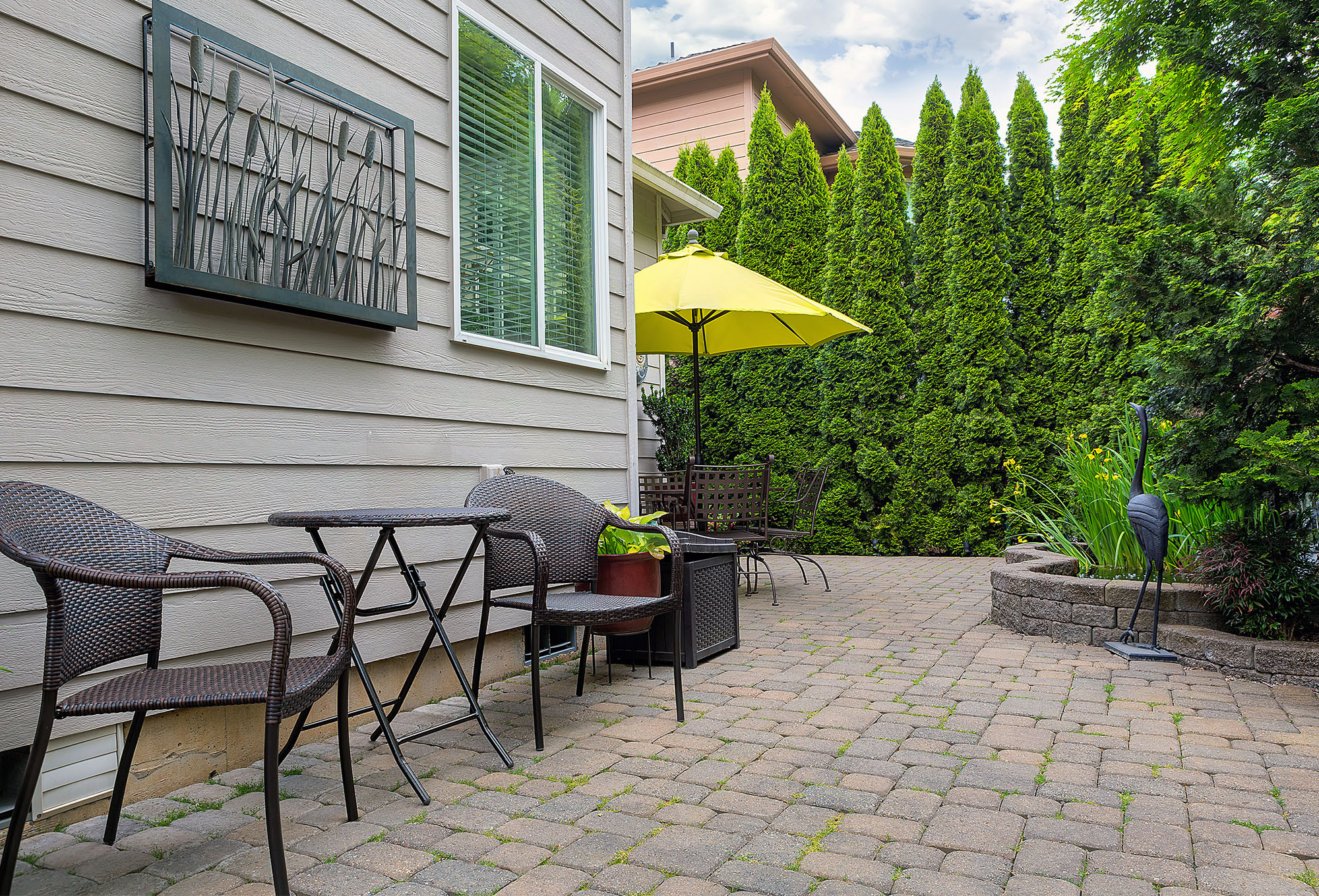 bistro table and chair on paver patio attached to house