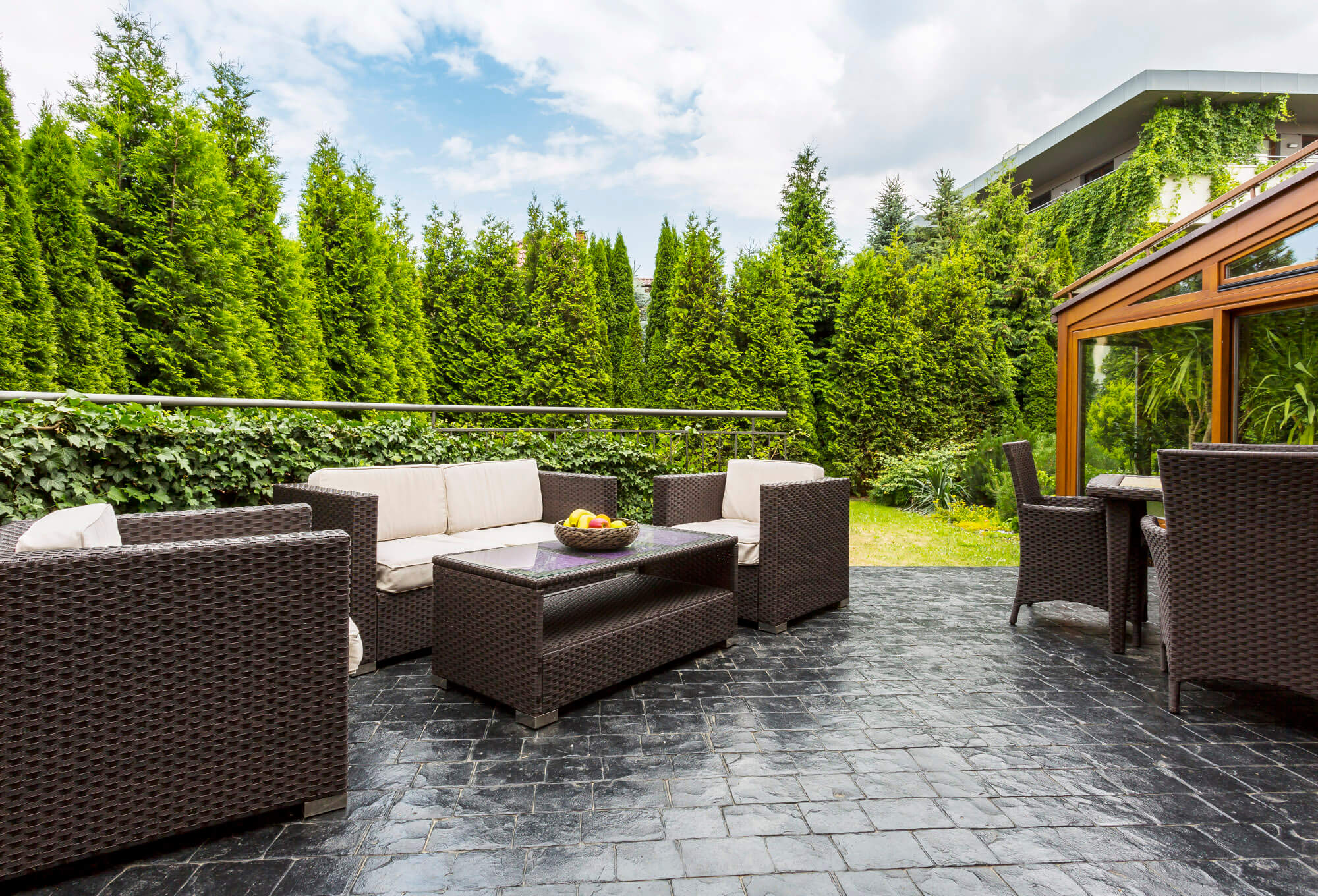Back patio with black tile and brown and tan whicker furniture surrounded by beautiful pine trees