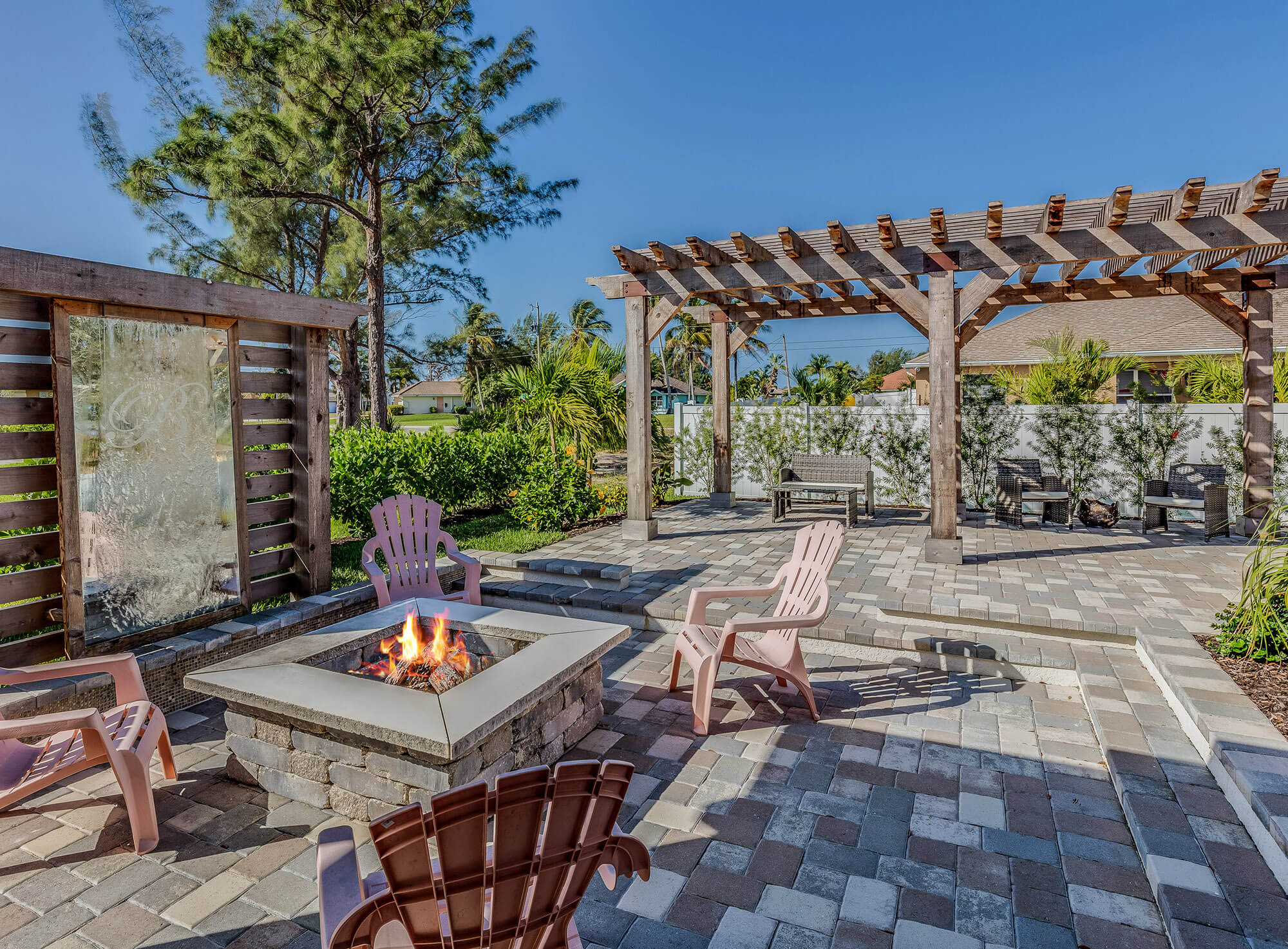 multi grey toned paver patio with fireplace and large wooden pergola