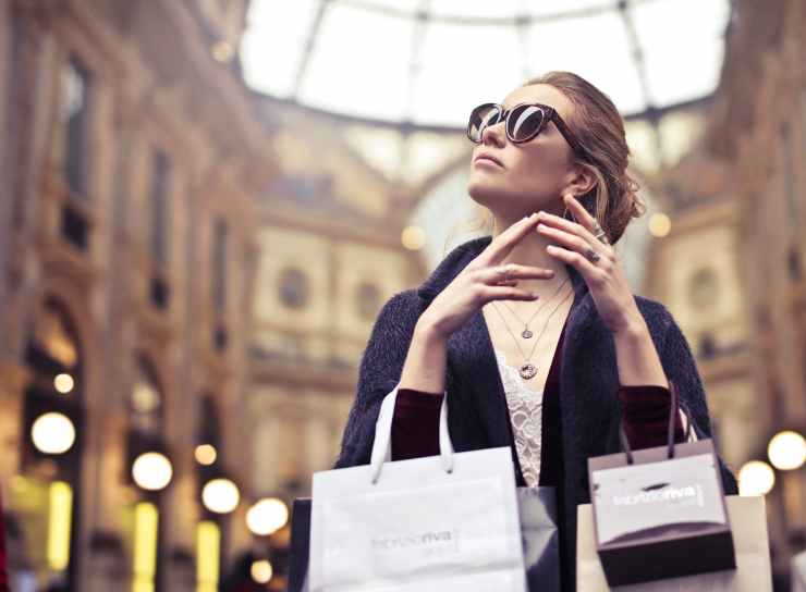 woman wearing sunglasses with assorted paper bags