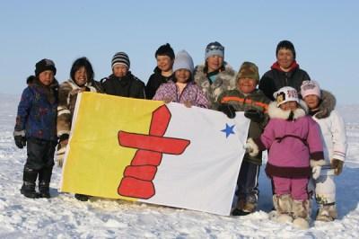 Nunavummiut standing behind Nunavut's flag.