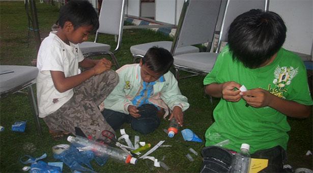 Beberapa anak sedang membuat roket air dengan botol bekas. Kredit: ALdino