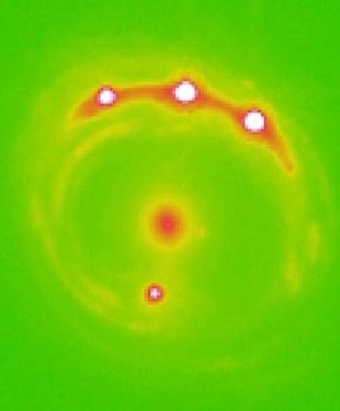 Pelensaan gravitasi Quasar RX J1131-1231 menghasilkan empat citra quasar di sekeliling galaksi. Kredit: Universitas Oklahoma