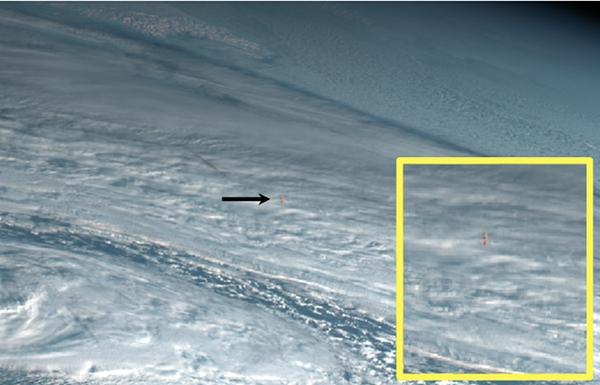 Gambar 2. Potongan citra satelit Himawari 8 pada kanal cahaya tampak untuk kawasan Samudera Pasifik bagian utara. Jejak Peristiwa Bering 2018 nampak jelas sebagai titik-titik cahaya berwarna kuning-jingga membentuk sebuah garis di antara tebaran awan-awan putih (tanda panah). Jejak diperbesar dalam gambar inset. Sumber: Japan Meteorology Agency, 2018.