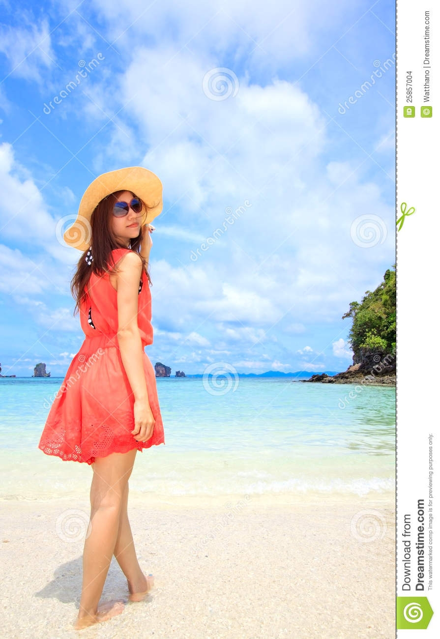 asian woman in a pink dress standing on the beach stock