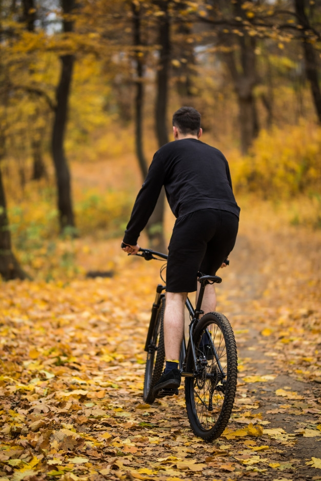 free photo back view of young handsome man riding a