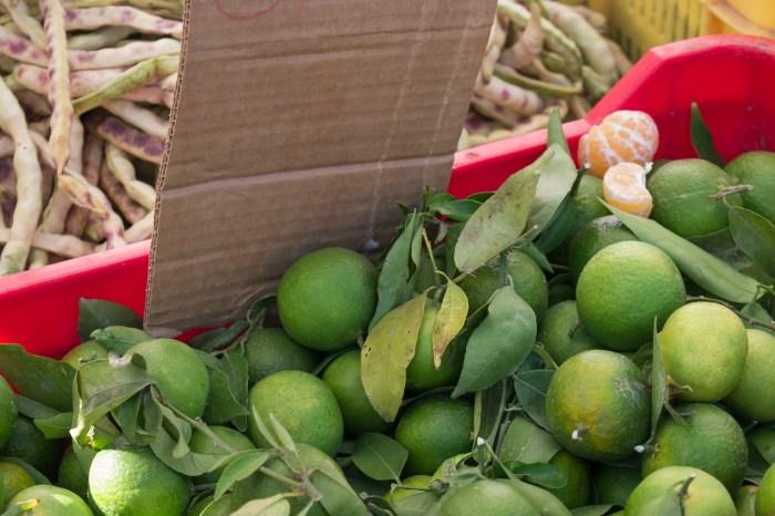 Местные зеленые, но очень сладкие мандарины и плоды рожкового дерева