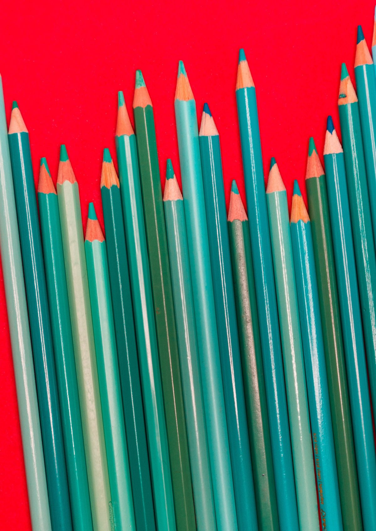 blue and green pencils against red background