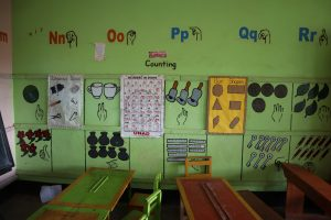 classroom with various teaching materials on the wall, including drawings of sign language for letters and numbers