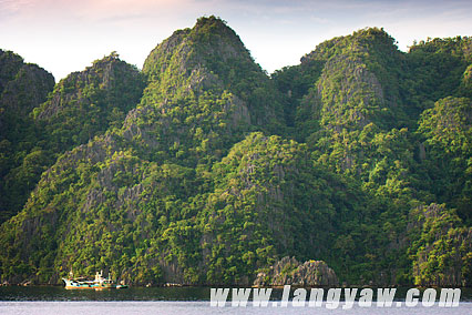 More karst limestone rock formations comprise the islands that seem to rise from the waters