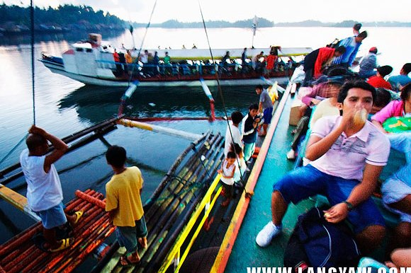 A man found a seat atop the pumpboat while other vessels are starting to sail to other islands near Masbate