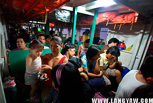 Inside the vessel, passengers are crowded with their things seated comfortably on wooden benches.