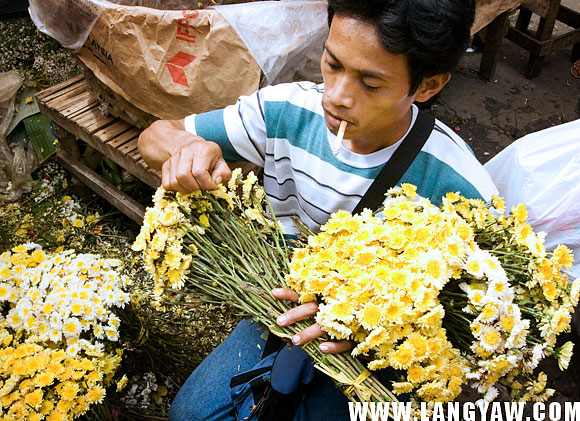A male flower vendor prepares a bouquet, usually by the dozen, at the streetside Carbon market.