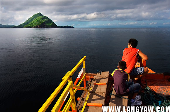 A man and a boy enjoying the wide expanse of sea and sky littered with virginal islets