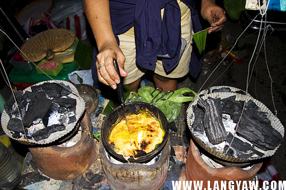 A bibingka being cooked and ready for selling as the sugar gets to caramelize and darken