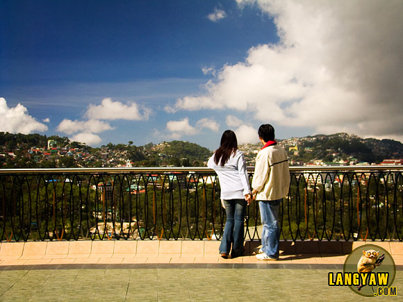 Two lovers gaze from the viewdeck of a mall in Baguio, enjoying the scene.
