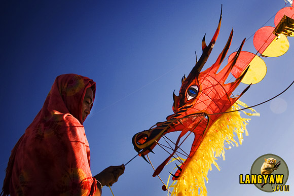 Taming the Dragon in Cebu. A kite flyer holding tightly his beast just after it flew.