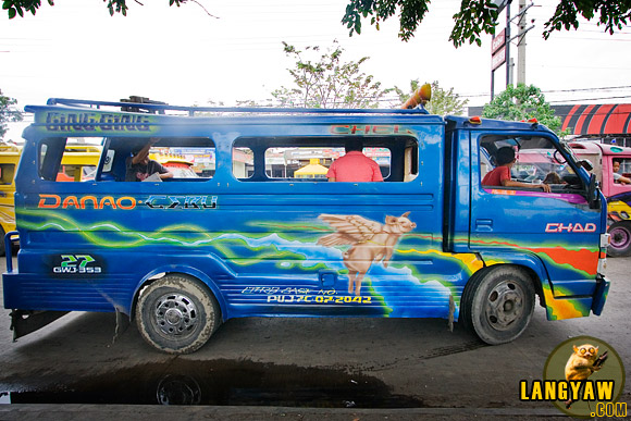 A flying pig decorates the body of another jeepney