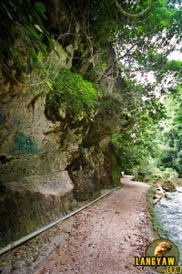 Dirt path to the waterfalls passes through rock walls and formations