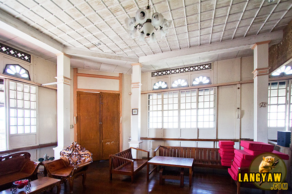 Interior of the Vargas Mansion with its coffered ceiling. Brown door opens to balcony.